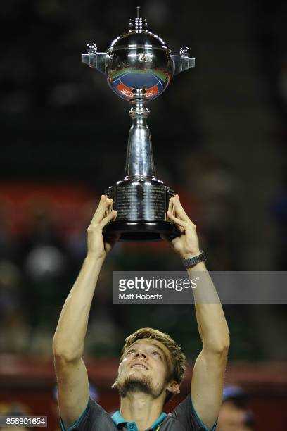 David Goffin of Belgium holds the winners trophy aloft after his men's final match against Adrian Mannarino of France during day seven of the Rakuten...
