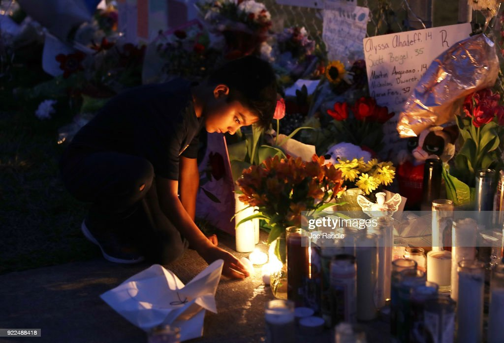 David Gomez,8, lights candles as he visits a makeshift memorial setup in front of Marjory Stoneman Douglas High School in memory of the 17 people that were killed on February 14, on February 21, 2018 in Parkland, Florida. Police arrested 19-year-old former student Nikolas Cruz for killing 17 people at the high school.