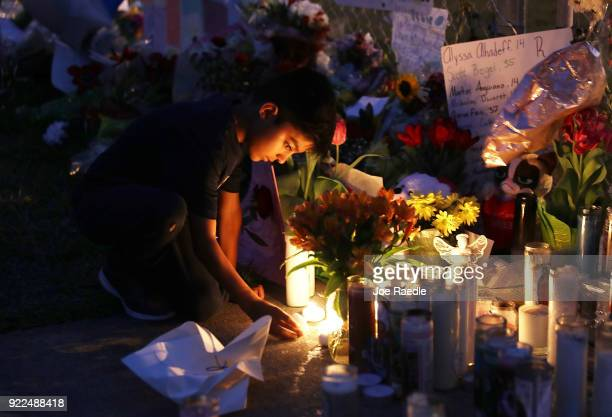 David Gomez lights candles as he visits a makeshift memorial setup in front of Marjory Stoneman Douglas High School in memory of the 17 people that...