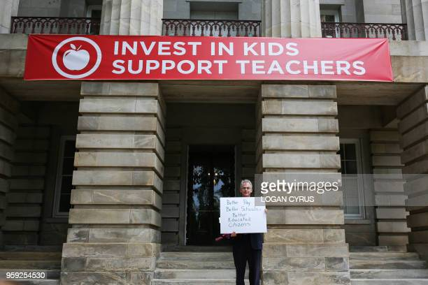 David Gould an art teacher in Onslow County North Carolina holds a sign outside under a banner that reads INVEST IN KIDS SUPPORT TEACHERS in the...