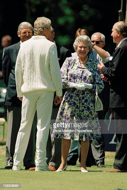 David Gower, captain of the Earl of Carnarvon's XI, talking to Her Majesty The Queen during an interval in the match between the Earl of Carnarvon's...