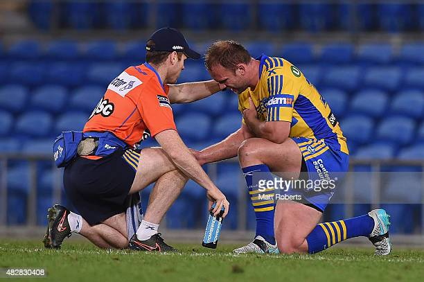 David Gower of the Eels receives attention from trainer Paul Devlin on the field during the round 21 NRL match between the Gold Coast Titans and the...