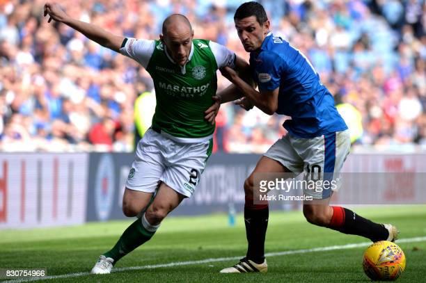 David Gray of Hibernian is tackled by Graham Dorrans of Rangers during the Ladbrokes Scottish Premiership match between Rangers and Hibernian at...