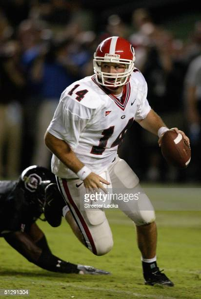 David Greene of the Georgia Bulldogs scrambles away from a South Carolina Gamecocks defender during their game at WilliamsBrice Stadium on September...