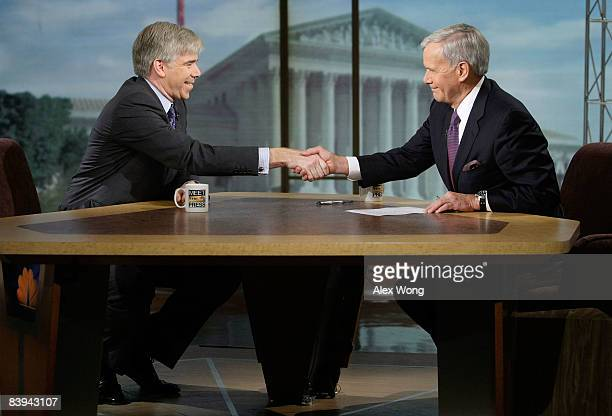 David Gregory shakes hands with interim moderator Tom Brokaw during a taping of 'Meet the Press' at the NBC studios December 7 2008 in Washington DC...