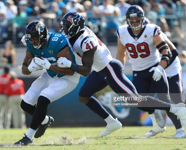 David Grinnage of the Jacksonville Jaguars is tackled by Zach Cunningham of the Houston Texans during the game at TIAA Bank Field on October 21 2018...