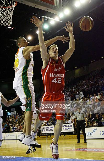 David Gruber of the Hawks is fouled by Russell Hinder of Townsville during the round 17 NBL match between the Wollongong Hawks and the Townsville...