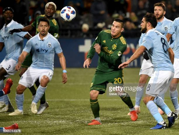 David Guzman of Portland Timbers heads a shot on goal as Roger Espinoza and Graham Zusi of Sporting Kansas City close in during the second half of...