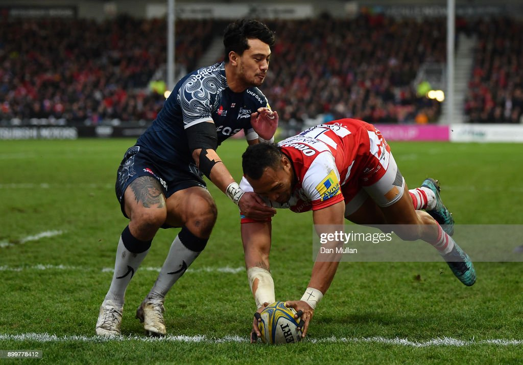 David Halaifonua of Gloucester dives over to score his side's first try past Denny Solomona of Sale Sharks during the Aviva Premiership match between Gloucester Rugby and Sale Sharks Sharks at Kingsholm Stadium on December 30, 2017 in Gloucester, England.
