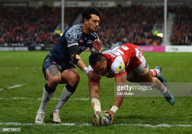 David Halaifonua of Gloucester dives over to score his side's first try past Denny Solomona of Sale Sharks during the Aviva Premiership match between...