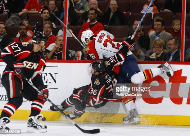 David Hale of the Ottawa Senators takes a big bodycheck along the far boards from Stever Bernier of the Florida Panthers during a game at Scotiabank...