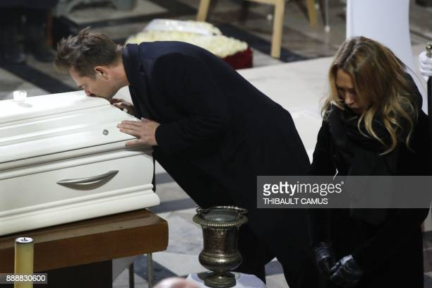 David Hallyday the son of late French singer Johnny Hallyday kisses the coffin of his father next to Laura Smet during the funeral ceremony for...