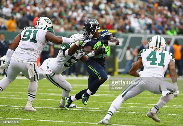 David Harris of the New York Jets pulls on the facemask of Christine Michael of the Seattle Seahawks as he attempts to tackle him in the third...