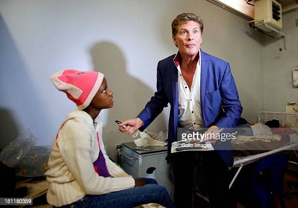 David Hasselhoff talks to young cancer patient Gaurupi Diretse at the Chris Hani Baragwanath hospital on August 31 2012 in Johannesburg South Africa...