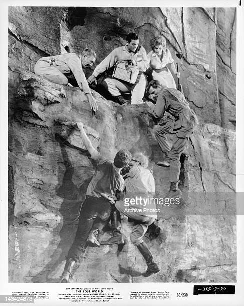 David Hedison and Jill St John watching Michael Rennie and others hanging from cliff in a scene from the film 'The Lost World' 1960