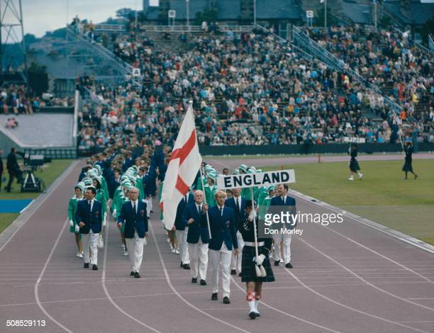 David Hemery carries the flag of England at the opening ceremony for the IX Commonwealth Games on 16th July 1970 at the Meadowbank Stadium in...