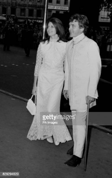 David Hemmings star of the film walking with a stick arrives with his wife actress Gayle Hunnicutt for the Royal gala premiere of Alfred the Great at...