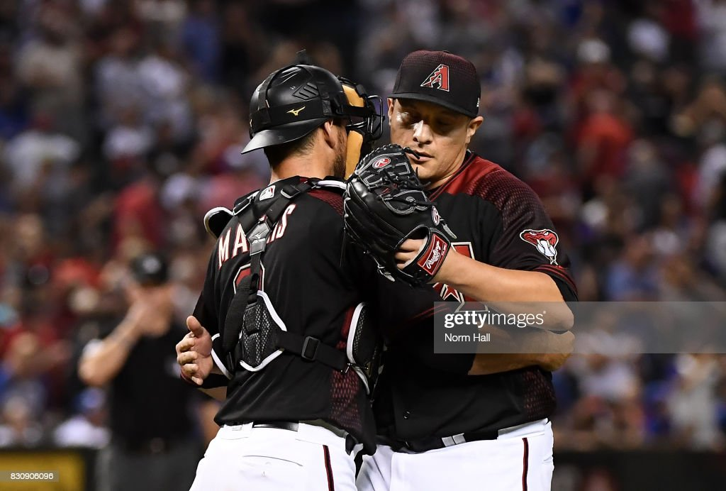 David Hernandez #47 and Jeff Mathis #2 of the Arizona Diamondbacks celebrate a 6-2 win against the Chicago Cubs at Chase Field on August 12, 2017 in Phoenix, Arizona.