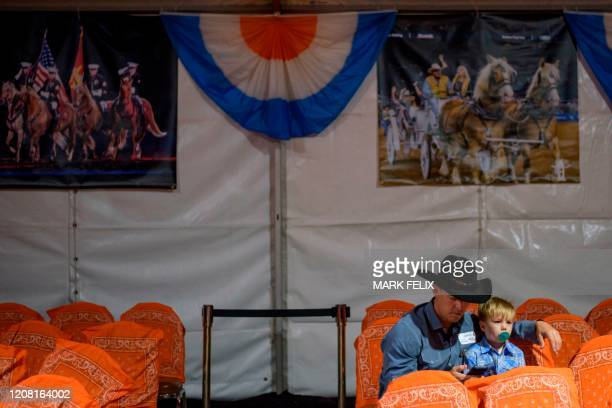 David Herr and his son Declan Herr sit together during the Houston Livestock Show and Rodeo on March 6, 2020 in Houston, Texas.