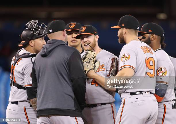 David Hess of the Baltimore Orioles reacts as manager Brandon Hyde visits the mound to make a pitching change as he is in the midst of a nohitter in...