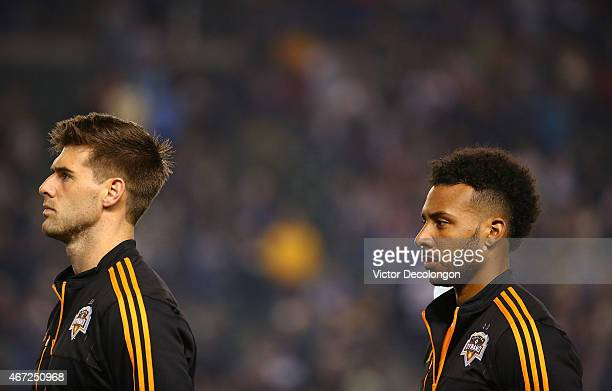 David Horst and Giles Barnes of Houston Dynamo look on during the singing of the national anthem prior to the MLS match against the Los Angeles...
