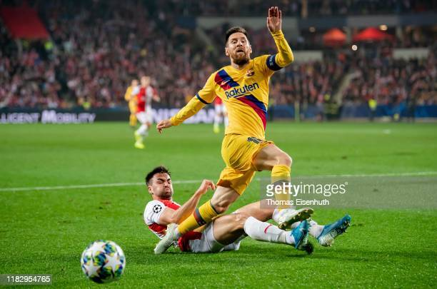 David Hovorka of Slavia Praha is challenged by Lionel Messi of Barcelona during the UEFA Champions League group F match between Slavia Praha and FC...