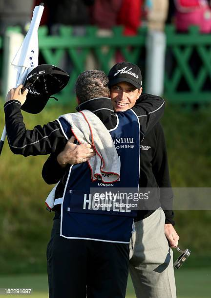 David Howell of England celebrates with his caddy after holing his putt on the 18th green during the second playoff hole against Peter Uihlein of the...