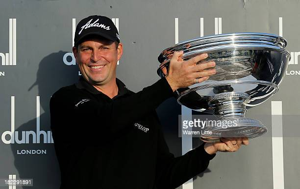 David Howell of England lifts the trophy aloft after victory at the Alfred Dunhill Links Championship on The Old Course at St Andrews on September 29...