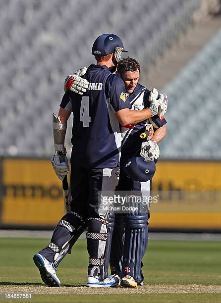 David Hussey of the Bushrangers celebrates his century with Andrew Mcdonald during the Ryobi One Day Cup match between Victorian Bushrangers and the...