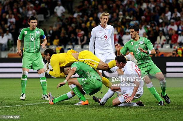 David James of England falls over Madjid Bougherra of Algeria as he makes a save during the 2010 FIFA World Cup South Africa Group C match between...