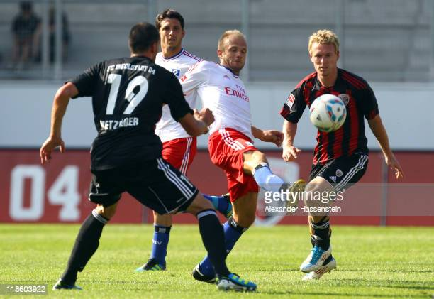 David Jarolim of Hamburg battles for the ball with Leonhard Haas of Ingolstadt and his team mate Malte Metzelder during the preseason friendly match...