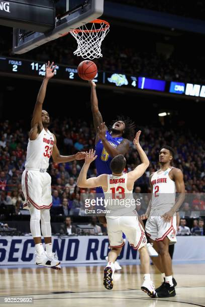 David Jenkins Jr #5 of the South Dakota State Jackrabbits drives to the basket against Keita BatesDiop and Andrew Dakich of the Ohio State Buckeyes...