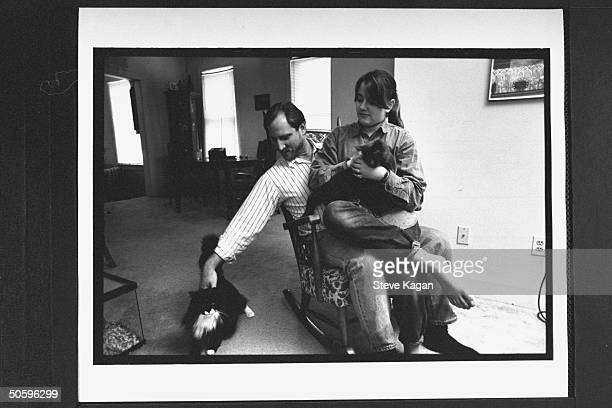 David Jewell petting one of two cats while his 12-yr-old daughter Kiri sits on his lap & pets the other in rocking chair at home; Jewell fought for...