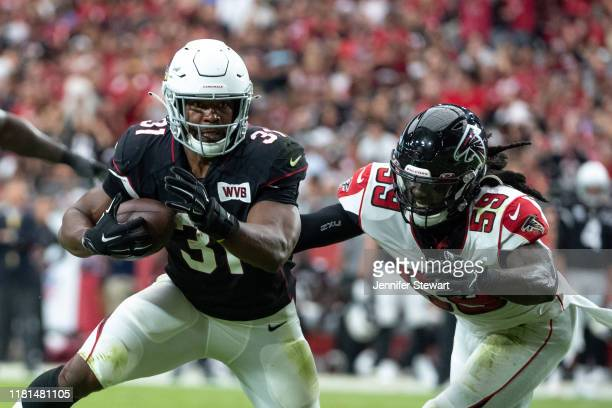 David Johnson of the Arizona Cardinals carries the ball against De'Vondre Campbell of the Atlanta Falcons during the NFL game at State Farm Stadium...