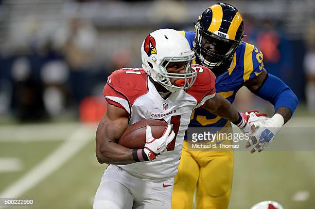 David Johnson of the Arizona Cardinals carries the ball while under pressure from Aaron Donald of the St Louis Rams in the third quarter at the...