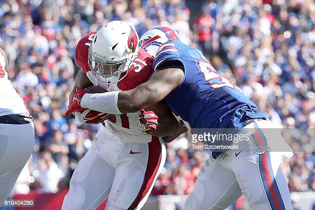 David Johnson of the Arizona Cardinals is tackled for a loss by Jerry Hughes of the Buffalo Bills during the second half at New Era Field on...