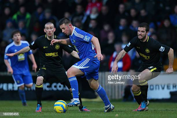 David Jones and Roman Golobart of Wigan Athletic marshall Waide Fairhurst of Macclesfield Town during the Budweiser FA Cup fourth round match between...