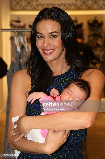 David Jones Brand Ambassador Megan Gale poses with a baby at the David Jones Malvern Central launch on September 12 2013 in Melbourne Australia