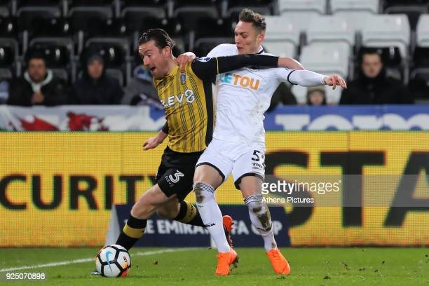 David Jones of Sheffield Wednesday challenged by Connor Roberts of Swansea City during The Emirates FA Cup Fifth Round Replay match between Swansea...