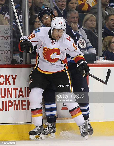 David Jones of the Calgary Flames and Blake Wheeler of the Winnipeg Jets collide along the boards in second period action in an NHL game at the MTS...
