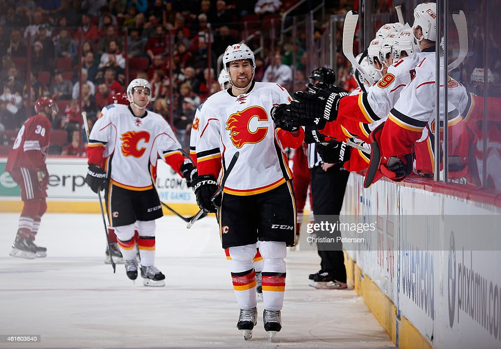 David Jones #19 of the Calgary Flames celebrates with teammates on the bench after scoring a third period goal against the Arizona Coyotes during the NHL game at Gila River Arena on January 15, 2015 in Glendale, Arizona. The Flames defeated the Coyotes 4-1.