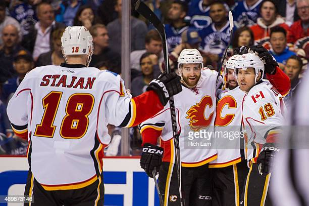 David Jones of the Calgary Flames is congratulated by TJ Brodie Michael Ferland and Matt Stajan after scoring a goal against the Vancouver Canucks in...