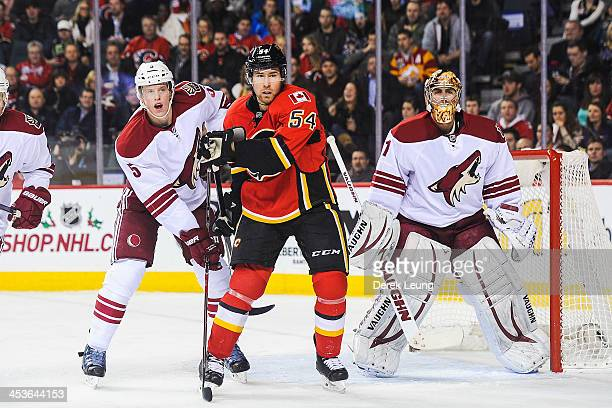 David Jones of the Calgary Flames looks for an opportunity as Connor Murphy and Thomas Greiss of the Phoenix Coyotes defend during an NHL game at...