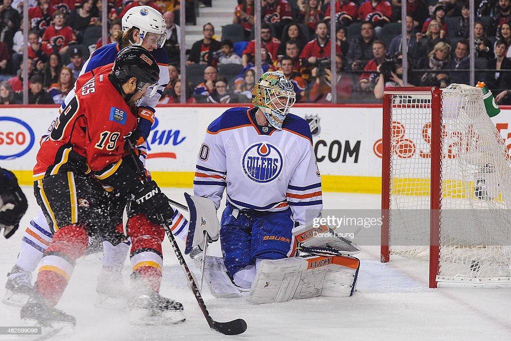 David Jones #19 of the Calgary Flames watches the shot of his teammate Lance Bouma #17 fly past Ben Scrivens #30 of the Edmonton Oilers during an NHL game at Scotiabank Saddledome on January 31, 2015 in Calgary, Alberta, Canada. The Flames defeated the Oilers 4-2.