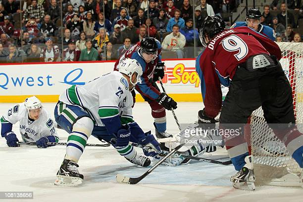 David Jones of the Colorado Avalanche collects the puck in front of Manny Malhotra and Alexander Edler of the Vancouver Canucks and scores the game...