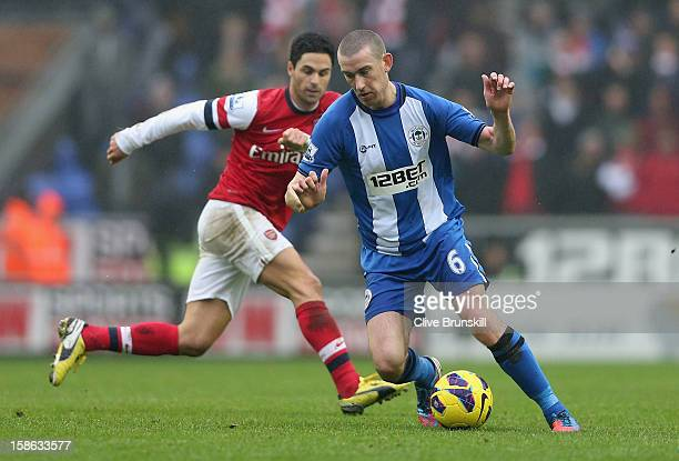 David Jones of Wigan Athletic competes with Mikel Arteta of Arsenal during the Barclays Premier League match between Wigan Athletic and Arsenal at...