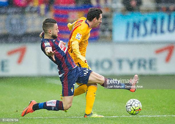 David Junca of SD Eibar duels for the ball with Lionel Messi FC Barcelona during the La Liga match between SD Eibar and FC Barcelona at Ipurua...