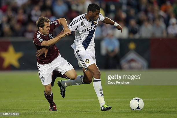 David Junior Lopes # of the Los Angeles Galaxy controls the ball while under pressure from Brian Mullen of the Colorado Rapids at Dick's Sporting...