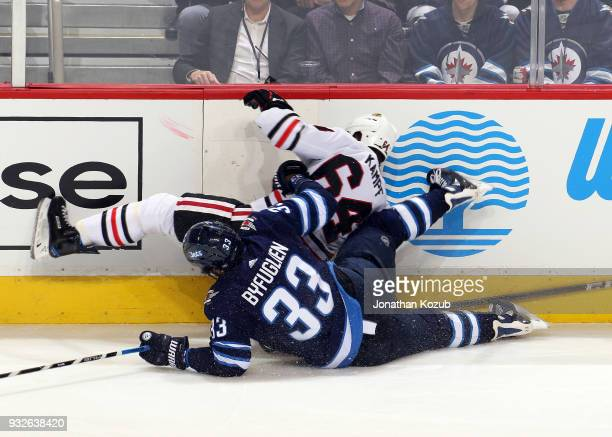 David Kampf of the Chicago Blackhawks and Dustin Byfuglien of the Winnipeg Jets fall to the ice after colliding along the boards during third period...