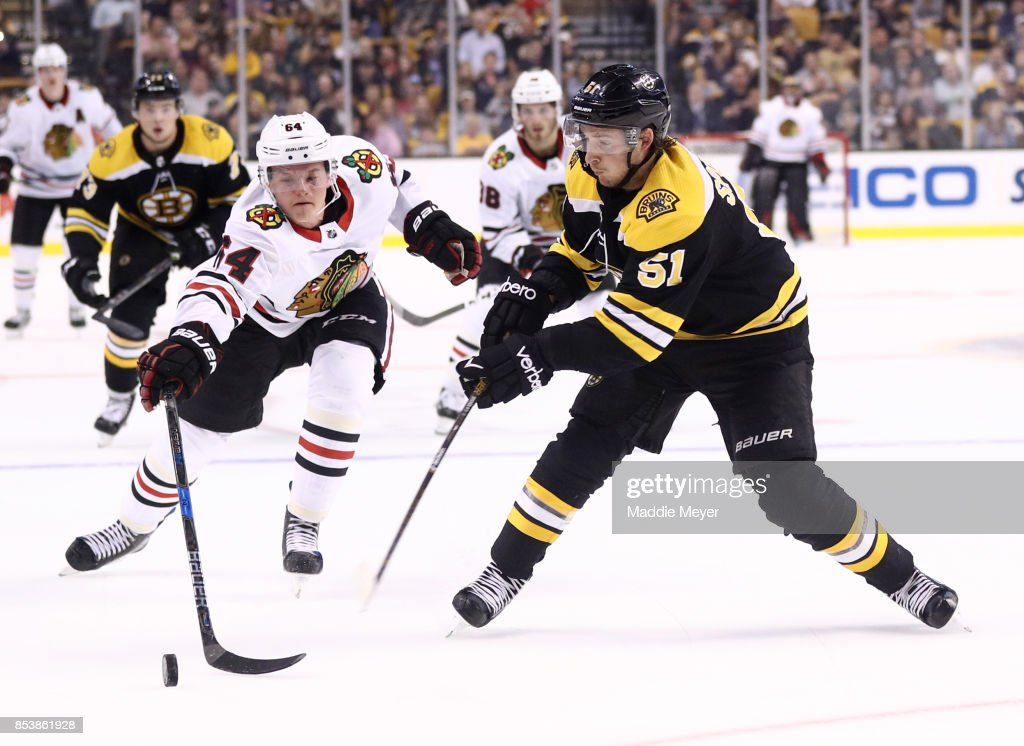 David Kampf #64 of the Chicago Blackhawks and Ryan Spooner #51 of the Boston Bruins battle for control of the puck during the second period at TD Garden on September 25, 2017 in Boston, Massachusetts.